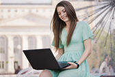Meisje met laptop buiten — Stockfoto
