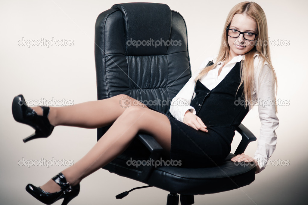 Cute business lady trying to relax in chair by sitting unusual in it  Stock Photo #9118402