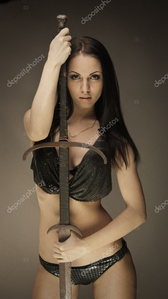 Portrait of gorgeous brunette woman with long rusty sword  Stock Photo #9776677