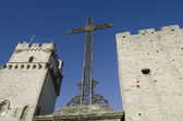 Christian cross between two medieval towers — Stock Photo