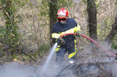 Firefighter fighting fire — Stock Photo
