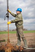 Worker in the oil industry on oil pump — Stockfoto