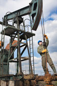 Worker in the oil industry on oil pump — Stock Photo