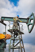 Worker in the oil industry on oil pump — Стоковое фото