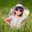 A beautiful little girl with a hat in a grain field — Stock Photo