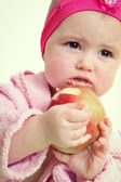 Baby holding and eating an apple, isolated on white — Stock Photo