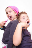 An adorable little boy and girl brushing his teeth on white background — Stock Photo