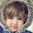 Beautiful little girl with fur hood in the snow — Stock Photo
