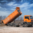 Orange truck unloading sand at site — Stock Photo #9527533