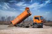 The orange truck unloading sand at the site — Stock Photo
