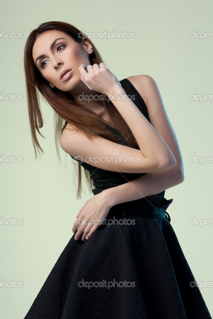Young brunette lady in black dress posing on grey background — Photo #9633027