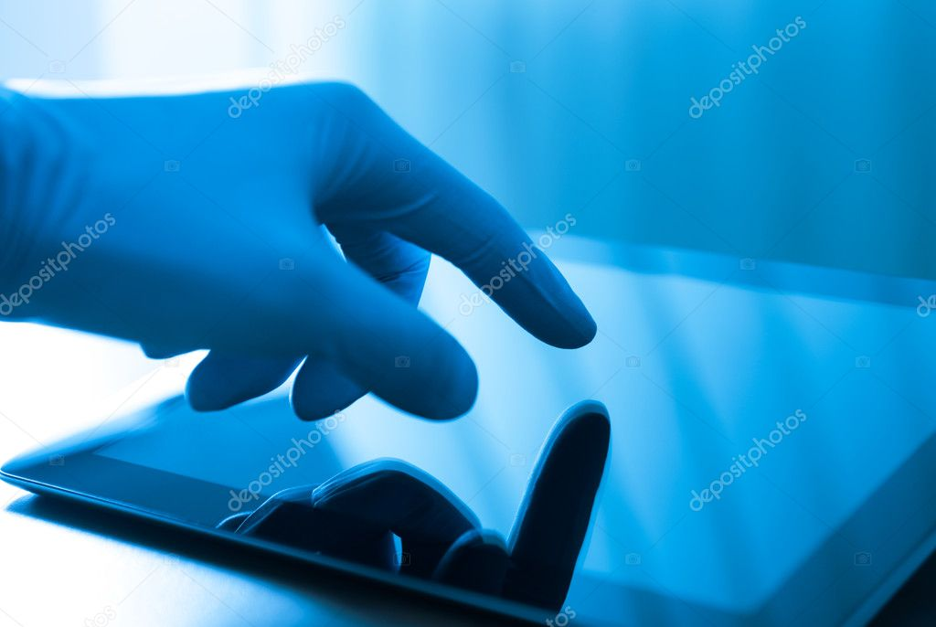 Hand in blue glove touching modern digital tablet. Concept image on medical or research theme. — Stock Photo #10488078