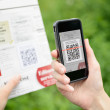 Scanning advertising with QR code on mobile phone — Stock Photo