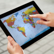 Stock Photo: Using World Map on Apple Ipad2