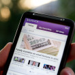 Hand holding HTC Desire HD showing Yahoo news — Stock Photo