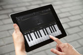 Play the piano at Apple Ipad2 — Stock Photo