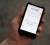 Hand hold HTC Desire HD with Google web page — Stock Photo