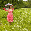 Young woman with red rose and umbrella on a meadow — Stock Photo