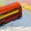 Royalty-Free Stock Photo: Red touristic bus on map of world