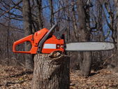 Orange chainsaw and woods — Stock Photo