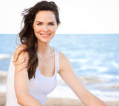 Beautiful healthy woman sitting on beach — Stock Photo