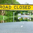 Road closed traffic sign on a flooded road - Stock Photo