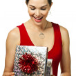 Attractive young woman looking in a gift box — Stock Photo