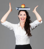 Woman balancing apple and books on head — Stock Photo