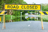Road closed traffic sign on a flooded road — Stock Photo