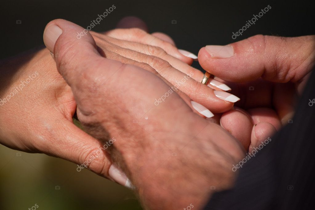 A closeup of a groom putting the ring on the brides finger during a wedding ceremony — Photo #10393415