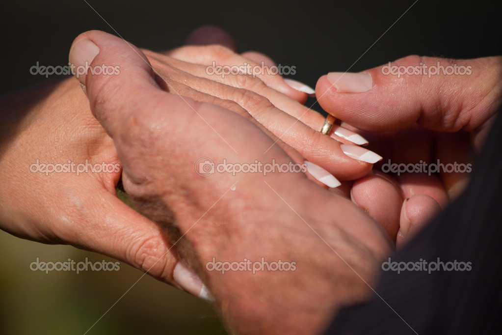 A closeup of a groom putting the ring on the brides finger during a wedding ceremony — Lizenzfreies Foto #10393415