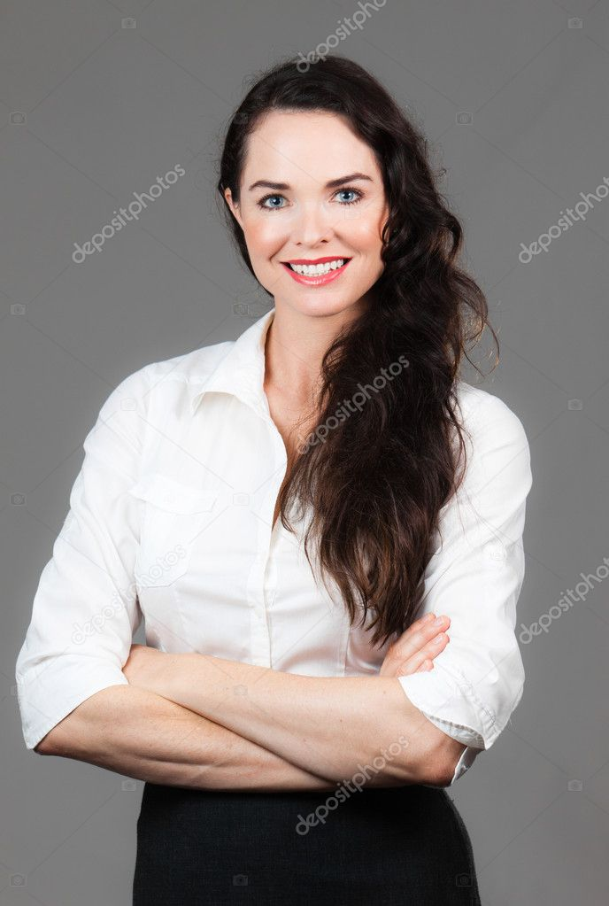 Portrait of a happy young business woman with arms folded, over grey background — Stock Photo #9793388