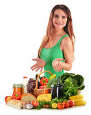 Young woman with basket full of vegetables and fruits — Stockfoto