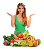 Young smiling woman with variety of fresh vegetables and fruits — Stock Photo