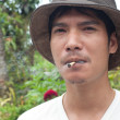 Asian man smoke thai traditional cigarette — Stock Photo