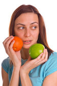 Young woman holding apple and orange over white — Stock Photo