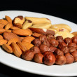 Hazelnuts, Brazil nuts, almonds, lie on the white plate on a black backgrou — Stock Photo