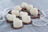 Heart-shaped chocolates with candies in coconut flakes of beads — Stock Photo