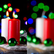 Red and white candle with a green New Year's ball on the background of lights — Stockfoto