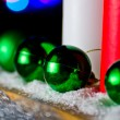 Red and white candle with a green New Year's ball on the background of lights - Stock Photo