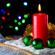 Red candle with a green New Year's ball on the background of lights - Stock Photo