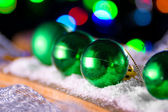 A green New Year's ball on the background of lights — Stok fotoğraf