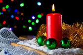 красная свеча с зеленый новогодний шар на фоне огни — Стоковое фото