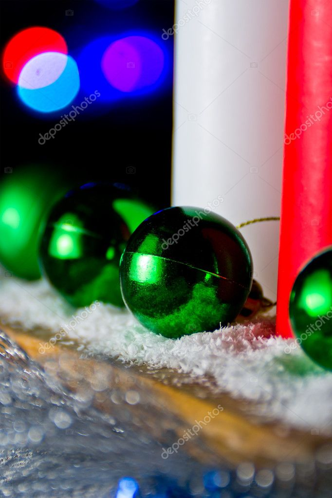 Red and white candle with a green New Year's ball on the background of lights — Stock Photo #9287465