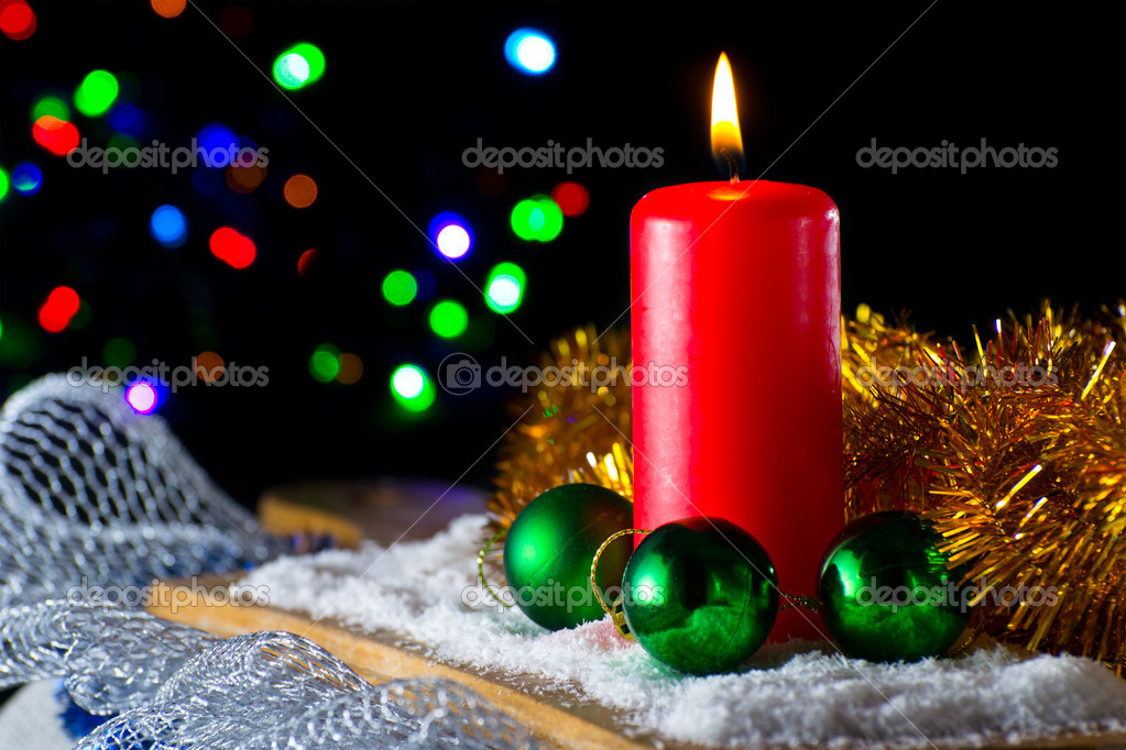 Red candle with a green New Year's ball on the background of lights — Foto Stock #9287470
