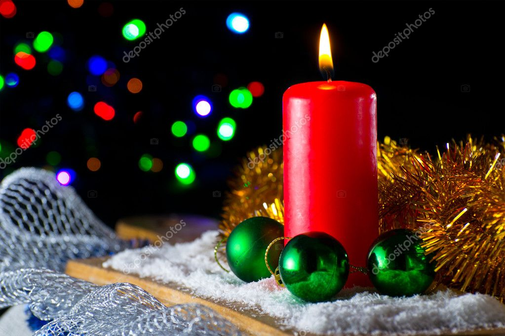 Red candle with a green New Year's ball on the background of lights — Stok fotoğraf #9287470