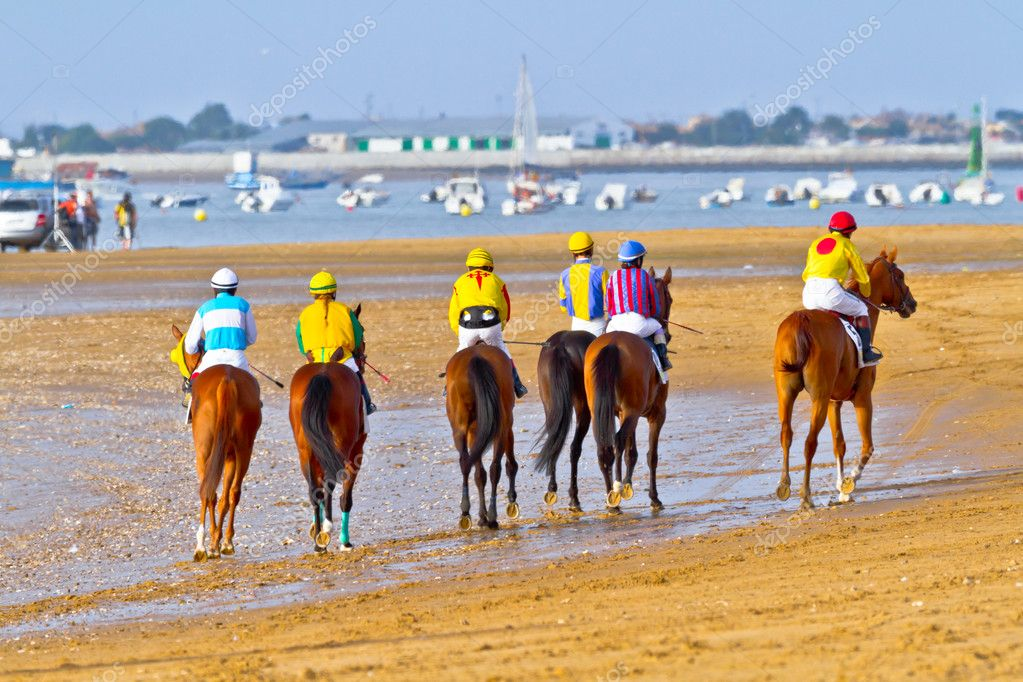 SANLUCAR DE BARRAMEDA, CADIZ, SPAIN - AUGUST 11: Unidentified riders at the start of race horses on Sanlucar de Barrameda beach on August 11, 2011 in Sanlucar d  Stock Photo #8066261