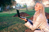 Beautiful blonde student girl in autumn park — Stock Photo