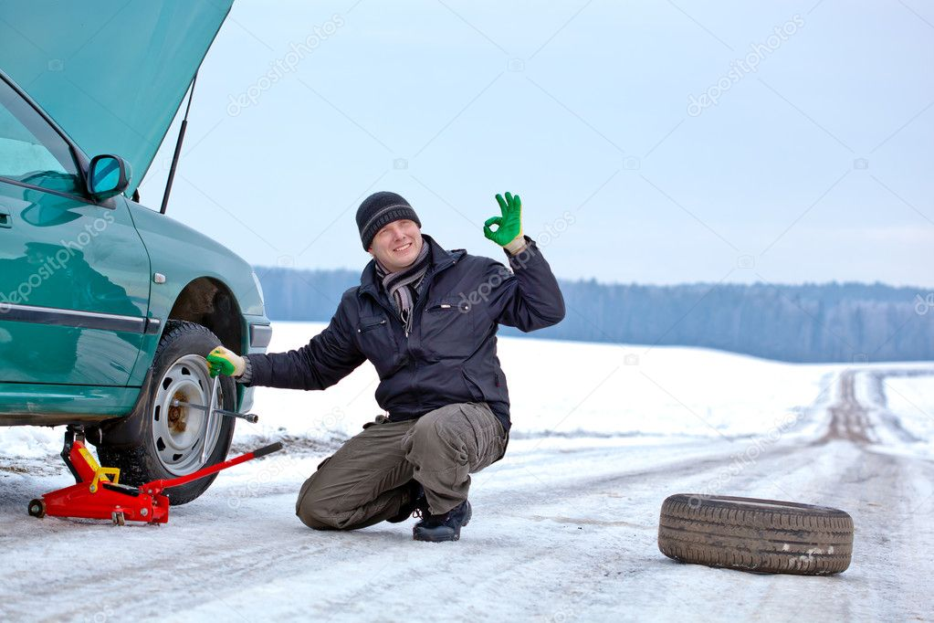 Man driver having trouble at a road changing wheel repairing car and giving okay sign hand gesture — Stock Photo #8426207
