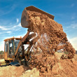Wheel loader unloading soil at construction site — Stock Photo #8461420